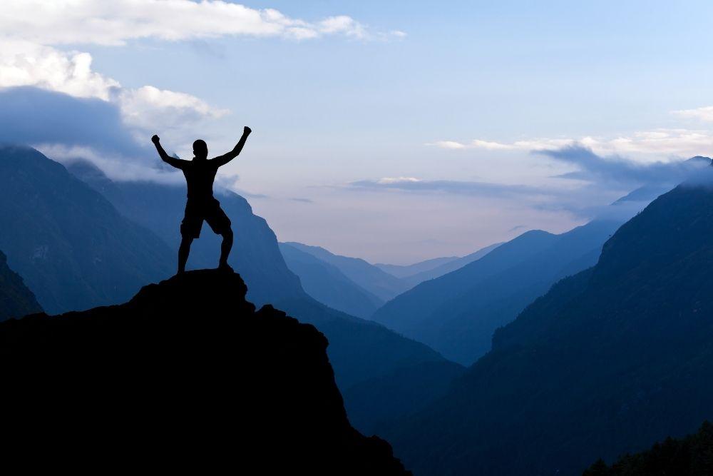 Características de um bom negócio - Homem em topo de montanha